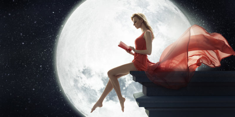 Woman reading a book by the light of the moon.