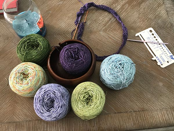 Yarn in six colors, purple, lighter purple, blue, green, green with orange flecks, and emerald green.