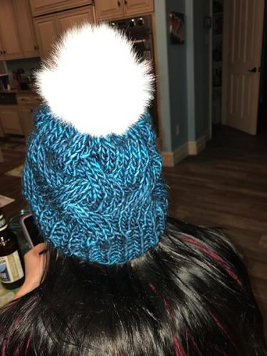 Kid 1 in a knitted blue hat with a pompom